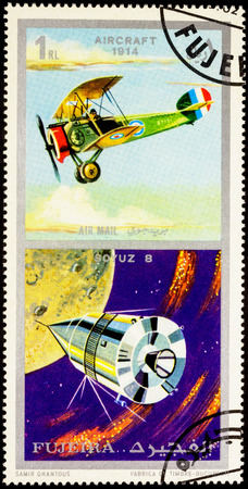 fujeira: MOSCOW, RUSSIA - APRIL 09, 2016: A stamp printed in Fujeira shows Russian spacecraft Soyuz 8 and ancient aircraft (1914), series Air and Space Vehicles, circa 1971