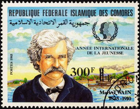 """humanismo: Mosc�, Rusia - 03 DE MAYO DE, 2016: Un sello impreso en Comoras muestra el retrato de Mark Twain (1835-1910), dedicada a los 150 a�os del nacimiento, de la serie """"Aniversarios"""", alrededor de 1985"""