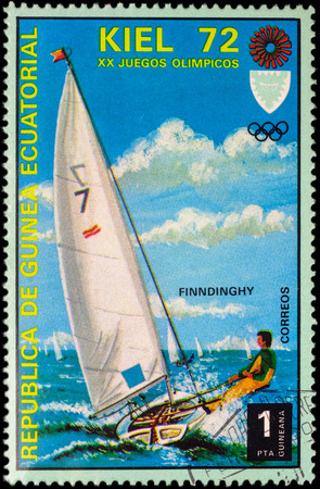 yachtsman: MOSCOW, RUSSIA - APRIL 27, 2016: A stamp printed in Equatorial Guinea shows yachting, the race in Finn class, series Olympic Games - Munich, Germany, circa 1972