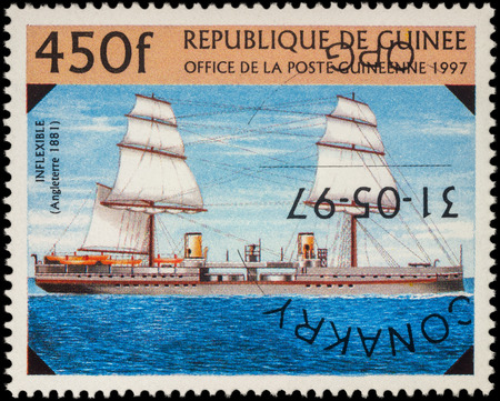 inflexible: MOSCOW, RUSSIA - MAY 08, 2016: A stamp printed in Guinea shows battleship of the Royal Navy Fleet UK Inflexible (1881), series The 19th-Century Warships, circa 1997