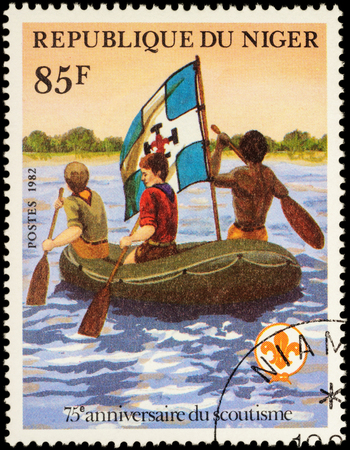 inflatable boat: MOSCOW, RUSSIA - MAY 14, 2016: A stamp printed in Niger shows three scout floating in an inflatable boat on the river, series The 75th Anniversary of Boy Scout Movement, circa 1982 Editorial