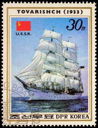 fock: MOSCOW, RUSSIA - MAY 17, 2016: A stamp printed in DPRK (North Korea) shows image of Russian sail training barque Tovarishch (1933) and flag of USSR, series Sailing Ships, circa 1987
