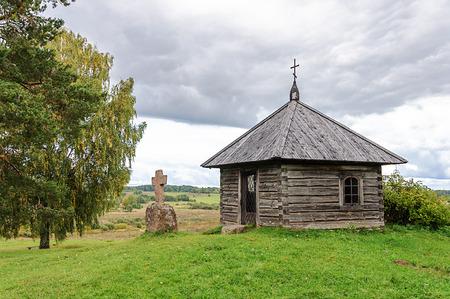 gory: Wooden chapel and stone cross on the top of Savkin hill, Pushkinskiye Gory Reserve, Russia