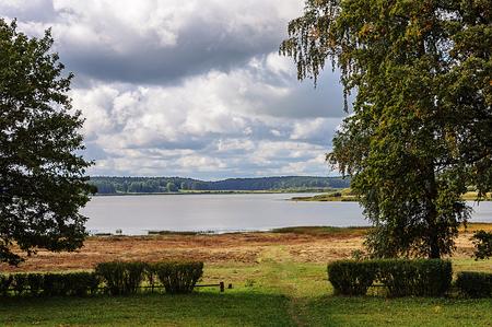 gory: View of lake Petrovskoye (Kuchane) with footpath in green grass, Pushkinskiye Gory Reserve, Russia Stock Photo