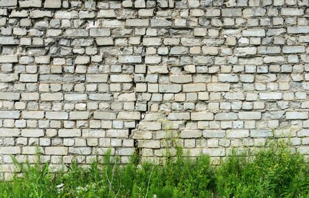 cracked wall: Background of old cracked white brick wall with green grass Stock Photo