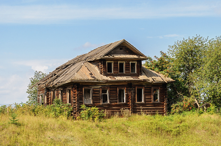 Old destroyed log wooden house in russian village, Vologda region. Sunny summer day