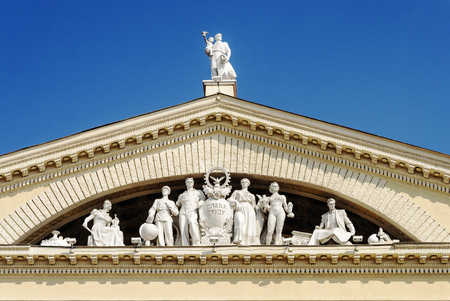 pediment: Fragment of classic ornate pediment with sculptures of people from Stalins era. Soviet architectural style. Trade union palace in Minsk, Belarus.