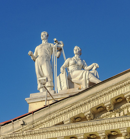 Sculpture of man with theodolite and sitting women on the roof of Trade Union Palace in Minsk, Belarus. Stalins era style.