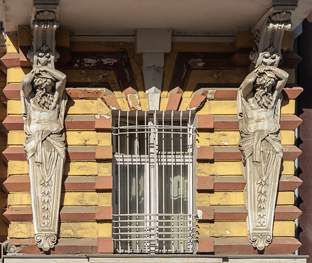 Window of old building with lattice and caryatids, Odessa, Ukraine Stock Photo