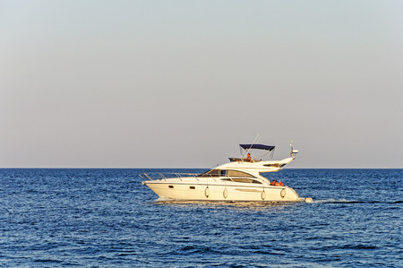 White luxury motor yacht under way out at the Black Sea in Odessa area, Ukraine. Summer evening.