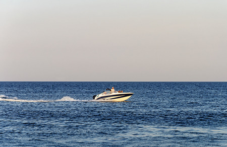 Small motor boat with tourists in the Black Sea near Odessa, Ukraine. Summer evening.
