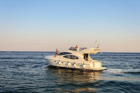 Odessa, Ukraine - September 04, 2016: Luxury white motor yacht under way out at the Black Sea. Summer evening.