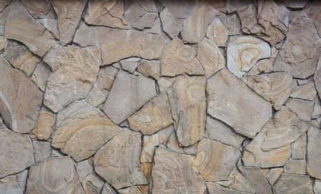facing a wall: Fragment of decorative brown facing of stone wall
