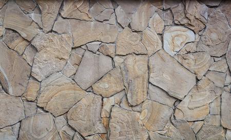 stonemason: Fragment of decorative brown facing of stone wall