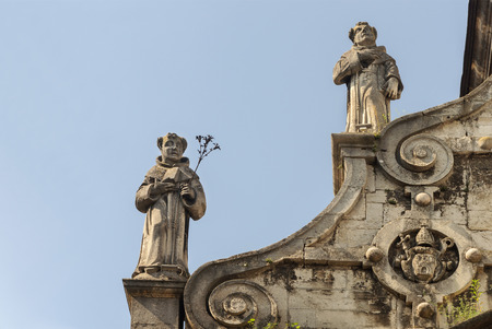 Two sculptures of monks on the roof of the catholic Bernardine church in Lviv (Lvov), Ukraine Stock Photo