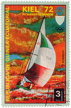 olympic games: MOSCOW, RUSSIA - January 09, 2017: A stamp printed in Equatorial Guinea shows yachting, the race in Soling class, series Olympic Games - Munich, Germany, circa 1972