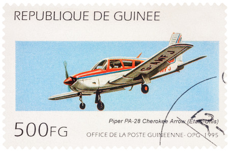 MOSCOW, RUSSIA - January 11, 2017: A stamp printed in Guinea shows aircraft Piper PA-28R-180 Cherokee Arrow in flight, series Aircraft, circa 1995 Editorial