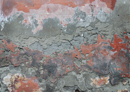 Texture of old damaged plaster wall with peeling red paint