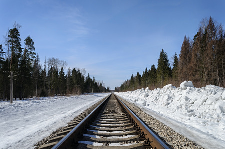 Railroad in snow-covered forest in early spring Stock Photo