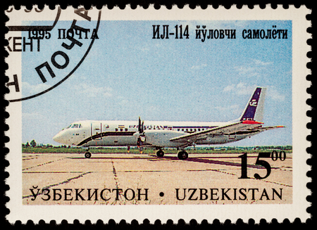 postmark: Moscow, Russia - July 05, 2017: A stamp printed in Uzbekistan shows airliner Ilyushin IL-114, series Aircraft of Tashkents Aircraft Factory, circa 1995 Editorial
