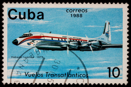 Moscow, Russia - July 14, 2017: A stamp printed in Cuba shows passenger airliner Douglas DC-7, Airline Havana-Luanda (1975), series The Cubana Airlines Transatlantic Flights, circa 1988