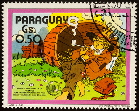 Moscow, Russia - July 30, 2017: A stamp printed in Paraguay shows Huckleberry Finn in the old barrel, Adventures of Tom Sawyer by Mark Twain, series International Year of Youth, circa 1985 Editorial