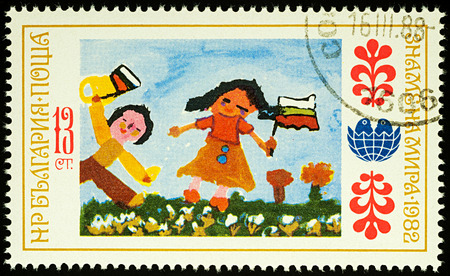 Moscow, Russia - August 03, 2017: A stamp printed in Bulgaria shows childrens drawing of Holiday, people with a flag, series International Childrens Assembly Banner of Peace, circa 1982