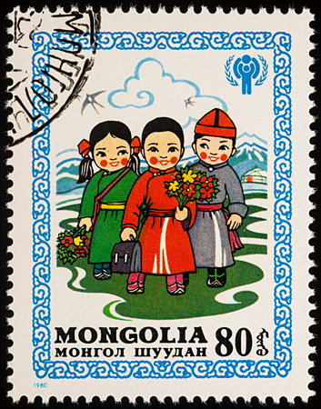 Moscow, Russia - August 05, 2017: A stamp printed in Mongolia, shows children in Mongolian national costumes with bouquets of flowers go to school, series