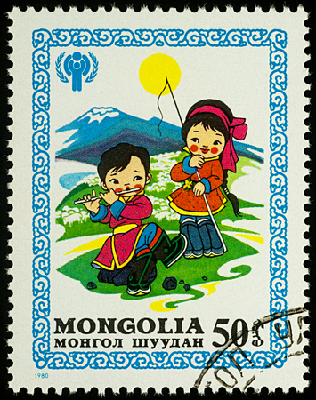 Moscow, Russia - August 05, 2017: A stamp printed in Mongolia, shows children, little boy and girl in traditional clothes on the pasture, series