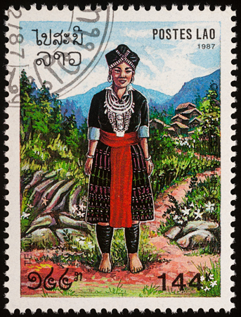 Moscow, Russia - August 06, 2017: A stamp printed in Laos, shows woman in a national Lao clothes against the backdrop of a mountain village, series Regional costumes, circa 1987 Editorial