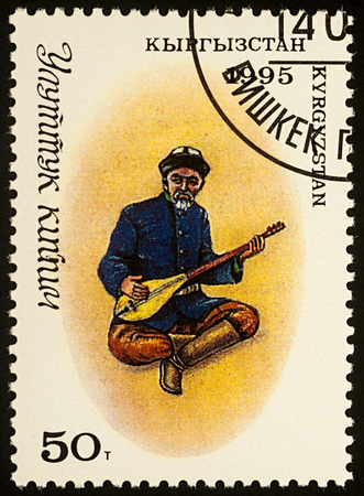 Moscow, Russia - August 07, 2017: A stamp printed in Kyrgyzstan, shows man in traditional Kyrgyz costume with a stringed musical instrument (comus), series Traditional Costumes, circa 1995