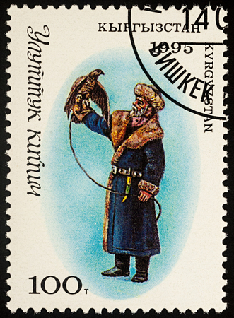 indigene: Moscow, Russia - August 07, 2017: A stamp printed in Kyrgyzstan, shows man-hunter in traditional clothes (fur coat) with a falcon, series
