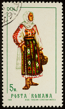 Moscow, Russia - August 08, 2017: A stamp printed in Romania, shows young woman in Romanian national costume, Dolj county, series