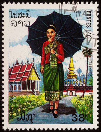 Moscow, Russia - August 06, 2017: A stamp printed in Laos, shows a woman in the national language Buddhist temple, series