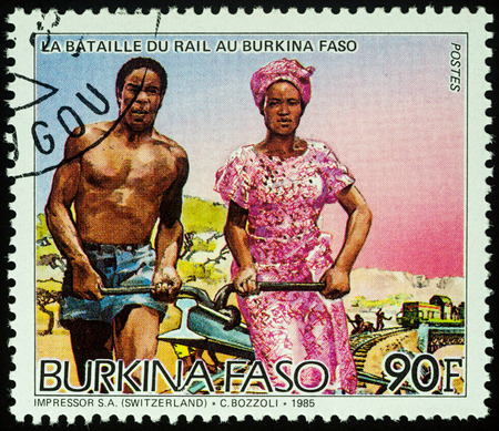 Moscow, Russia - August 07, 2017: A stamp printed in Burkina Faso, shows African man and woman carrying rail, series Railroad Construction, circa 1986