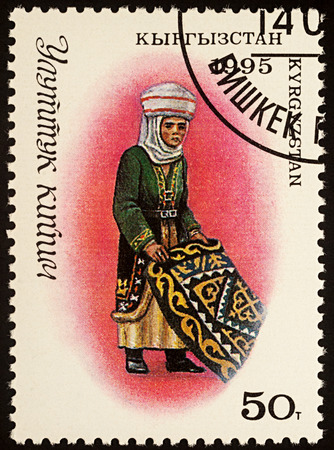 Moscow, Russia - August 07, 2017: A stamp printed in Kyrgyzstan, shows woman in traditional Kyrgyz costume with carpet, series Editorial