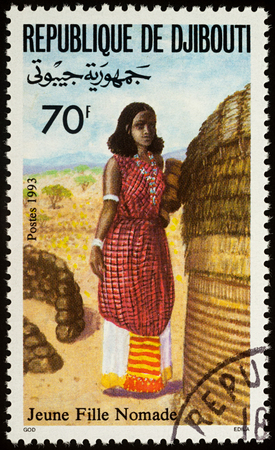 Moscow, Russia - August 06, 2017: A stamp printed in Djibouti, shows young woman in a national African clothes, series Traditional costumes, circa 1993 Editorial
