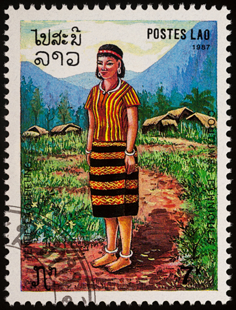 Moscow, Russia - August 06, 2017: A stamp printed in Laos, shows a woman in a national Lao clothes against the backdrop of a mountain village, series