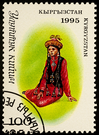 Moscow, Russia - August 07, 2017: A stamp printed in Kyrgyzstan, shows sitting young woman in a traditional Kyrgyz suit, series Traditional Costumes, circa 1995