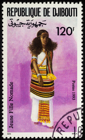 Moscow, Russia - August 06, 2017: A stamp printed in Djibouti, shows young nomadic woman in national African clothes, series Traditional costumes, circa 1993
