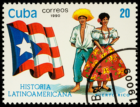 Moscow, Russia - August 10, 2017: A stamp printed in Cuba, shows national flag and a couple in traditional costumes of Puerto Rico, series Editorial