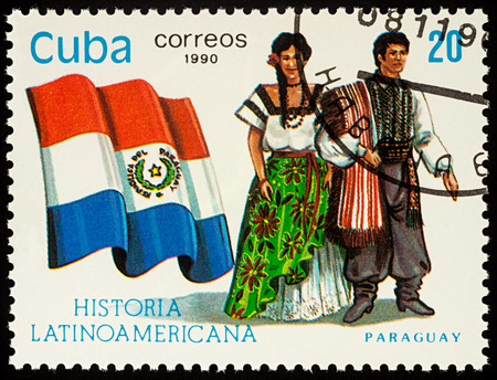 Moscow, Russia - August 10, 2017: A stamp printed in Cuba, shows national flag and a couple in traditional costumes of Paraguay, series