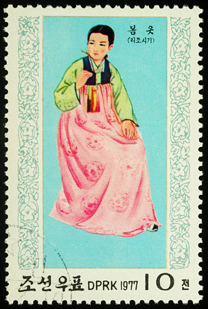 Moscow, Russia - August 09, 2017: A stamp printed in DPRK (North Korea), shows a woman in traditional Korean dress for spring, series National Costumes, circa 1977 Editorial