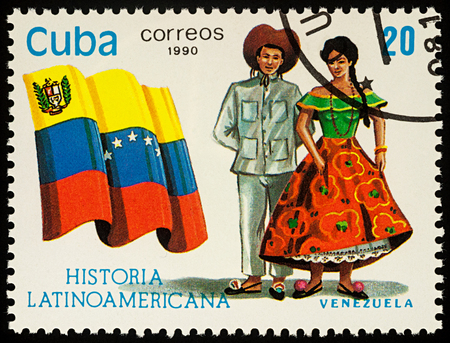 Moscow, Russia - August 10, 2017: A stamp printed in Cuba, shows national flag and a couple in traditional costumes of Venezuela, series