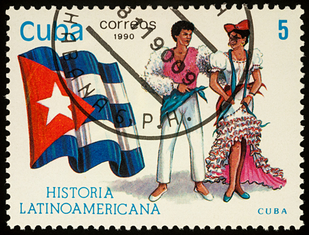 Moscow, Russia - August 10, 2017: A stamp printed in Cuba, shows national flag and a couple in traditional costumes of Cuba, series