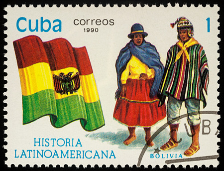 Moscow, Russia - August 09, 2017: A stamp printed in Cuba, shows national flag and a couple in Bolivian traditional costumes, series Editorial