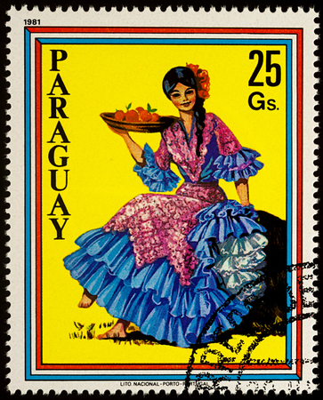 Moscow, Russia - August 09, 2017: A stamp printed in Paraguay, shows beautiful young woman in Paraguayan traditional dress with fruits, series