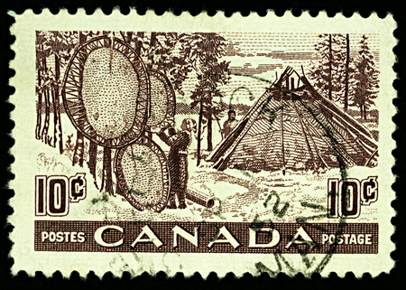 Moscow, Russia - November 23, 2017: A stamp printed in Canada shows native Indians drying animal skins, series