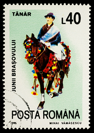 Moscow, Russia - January 03, 2018: A stamp printed in Romania, shows celebrating man riding on a decorated horse, Tanar, series Guilds of Brasov, circa 1995