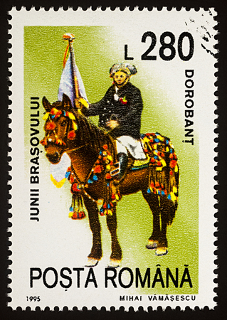 Moscow, Russia - January 04, 2018: A stamp printed in Romania, shows celebrating man with flag riding on a horse, Dorobant, series Guilds of Brasov, circa 1995